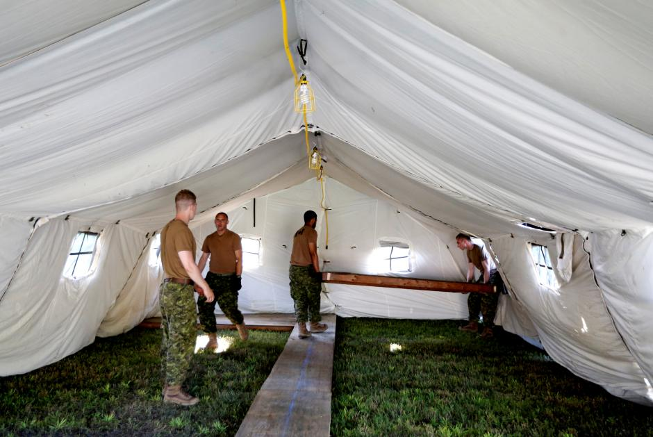 Members of the Canadian Armed Forces carry floorboards into the tents they erected to house asylum seekers at the Canada-United States border in Lacolle, Quebec, August 9, 2017. REUTERS/Christinne Muschi