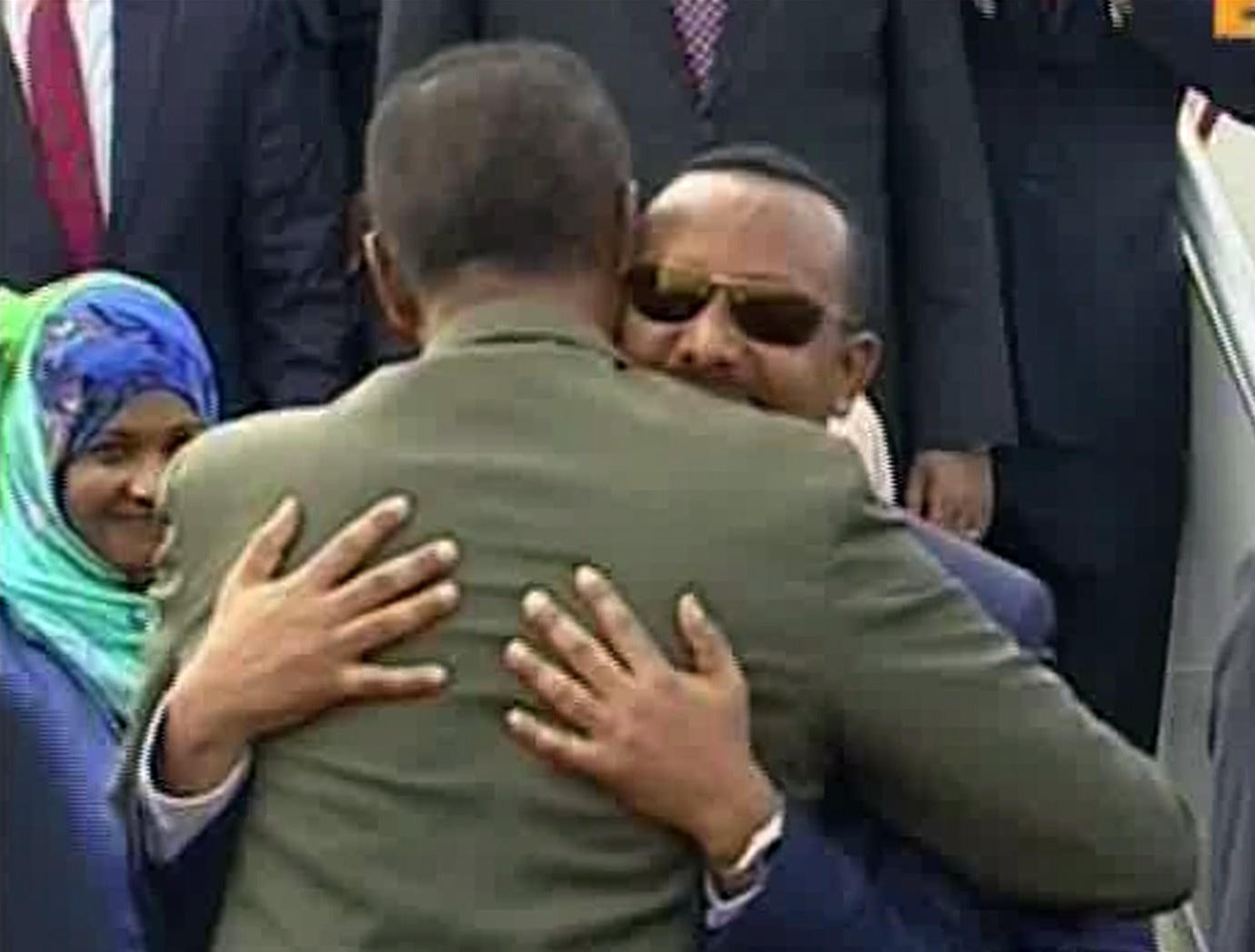 Ethiopian Prime Minister Abiy Ahmed, background, is welcomed by Eritrean President Isaias Afwerki as he disembarks a plane on Sunday in Asmara, Eritrea.
