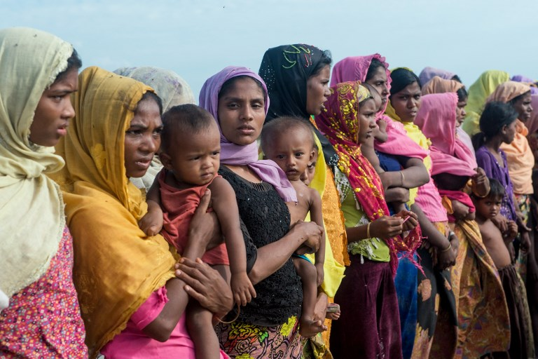 In this photograph taken on November 12, 2017, women hold children at a makeshift camp in Rakhine state in Myanmar, where hundreds of Rohingya Muslims wait in makeshift camps before finding a way to cross over into Bangladesh. Torched villages and unharvested paddy fields stretch to the horizon in Myanmar's violence-gutted Rakhine state, where a dwindling number of Muslim Rohingya remain trapped in limbo after a violent military crackdown coursed through the region. A rare military-organised trip for foreign media by helicopter to Maungdaw -- the epicentre of a crisis that exploded in late August -- showed a landscape devoid of people, with blackened patches marking the spots where Rohingya villages once stood.   / AFP PHOTO / Phyo Hein KYAW / TO GO WITH Myanmar-Bangladesh-refugee-unrest-economy-agriculture, SCENE by Hla-Hla HTAY
