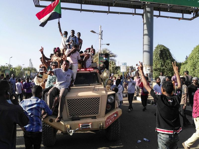 TOPSHOT - Sudanese protesters wave a national flag and flash the victory sign as they sit atop a military vehicle next to soldiers near the capital Khartoum's military headquarters on April 7, 2019, as they rally for a second day urging the military to back them. - Sudanese police fired tear gas at thousands of protesters who rallied outside the army headquarters for a second day urging the military to back them in demanding President Omar al-Bashir resign. (Photo by - / AFP)        (Photo credit should read -/AFP/Getty Images)