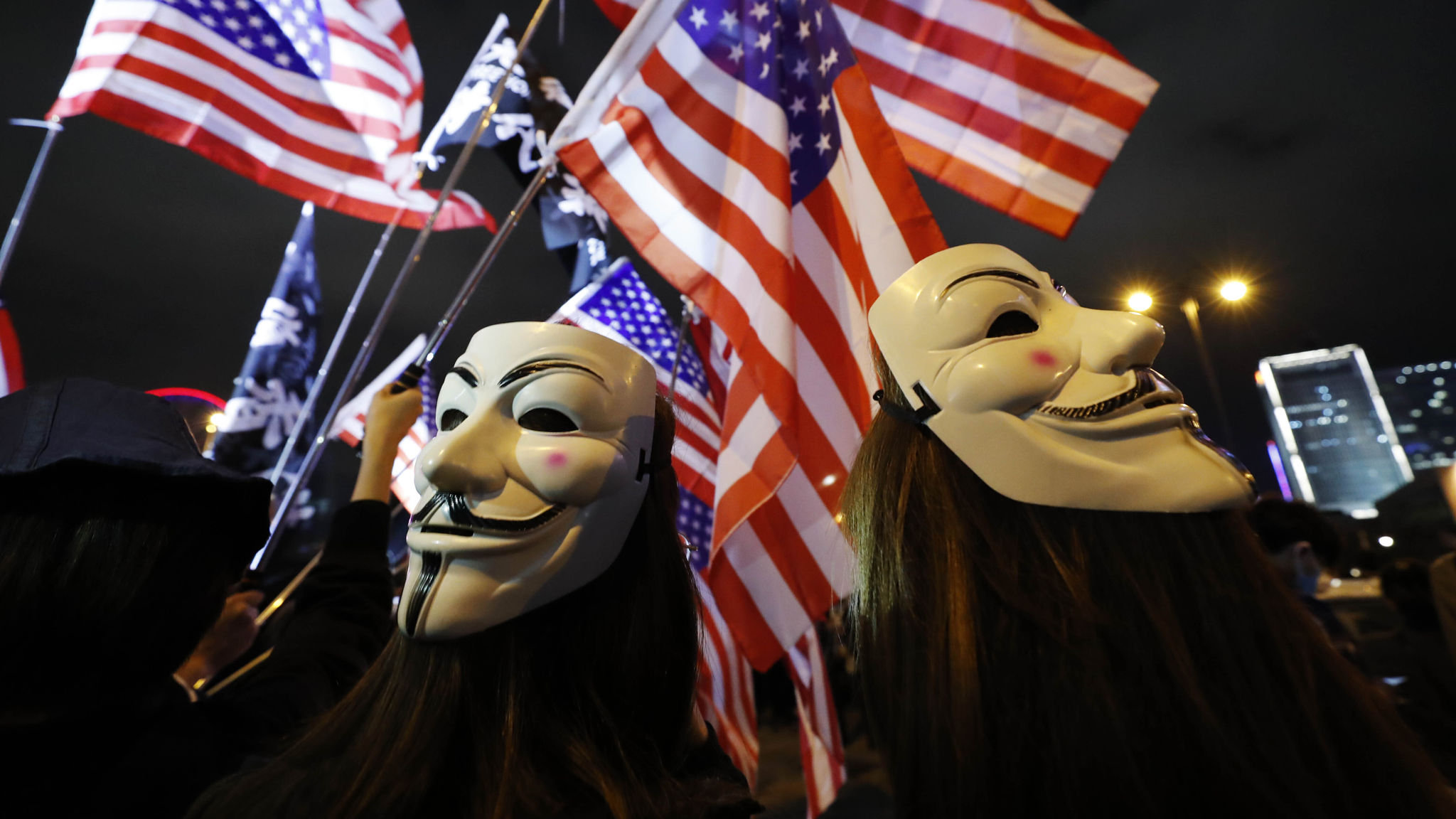 Protestors wear masks and hold U.S. flags in Hong Kong, Thursday, Nov. 28, 2019. China reacted furiously Thursday to President Donald Trump's signing of bills on Hong Kong human rights, summoning the U.S. ambassador to strongly protest and warning the move would undermine cooperation with Washington. Hong Kong, a former British colony that was granted special autonomy when China took control in 1997, has been rocked by six months of sometimes violent pro-democracy demonstrations. (AP Photo/Vincent Thian)