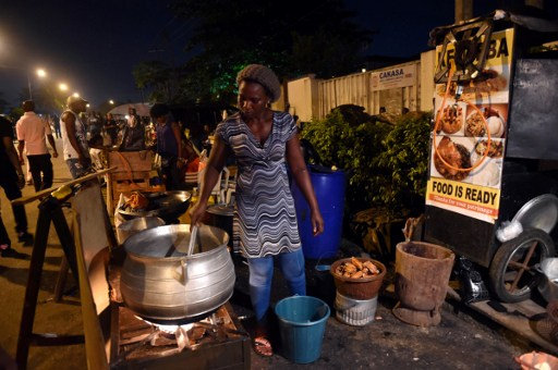 A vendor cooks food at a stand near the entrance of the  Felabration music festival in Lagos, on October 16, 2016.  Felabration is an annual music festival conceived in 1998 by Yeni Anikulapo-Kuti in memory and celebration of her father Fela Kuti, a Nigerian musician and human rights activist known for pioneering the afrobeat genre of music.  / AFP PHOTO / PIUS UTOMI EKPEI